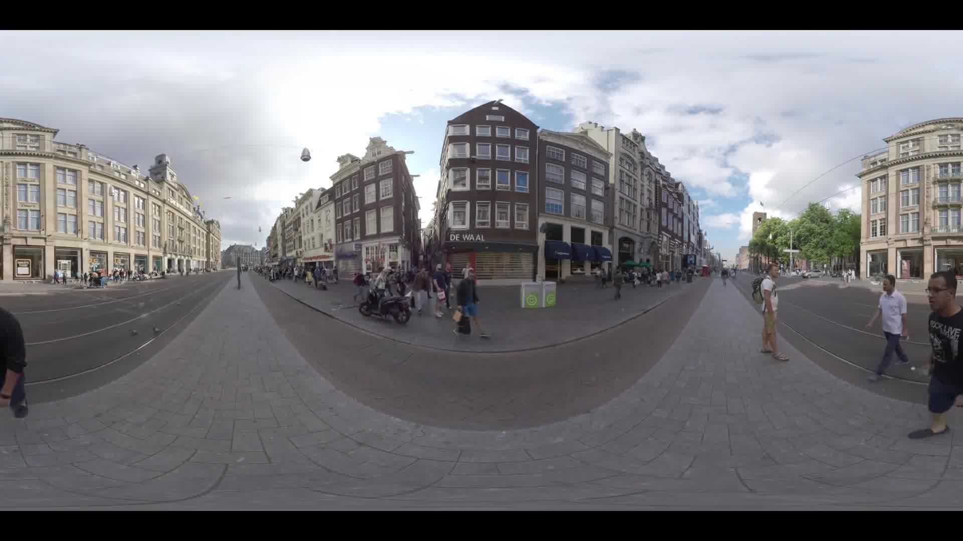 AMSTERDAM, NETHERLANDS - AUGUST 09, 2016: 360 VR video. View to Damrak avenue with tram rails, bike lanes and walking people. Street with lots of stores and cafes running between Amsterdam Centraal and Dam Square