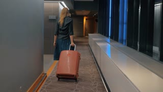 Back view of a woman rolling trolley case along the hotel hallway. She is going to get settled in the room