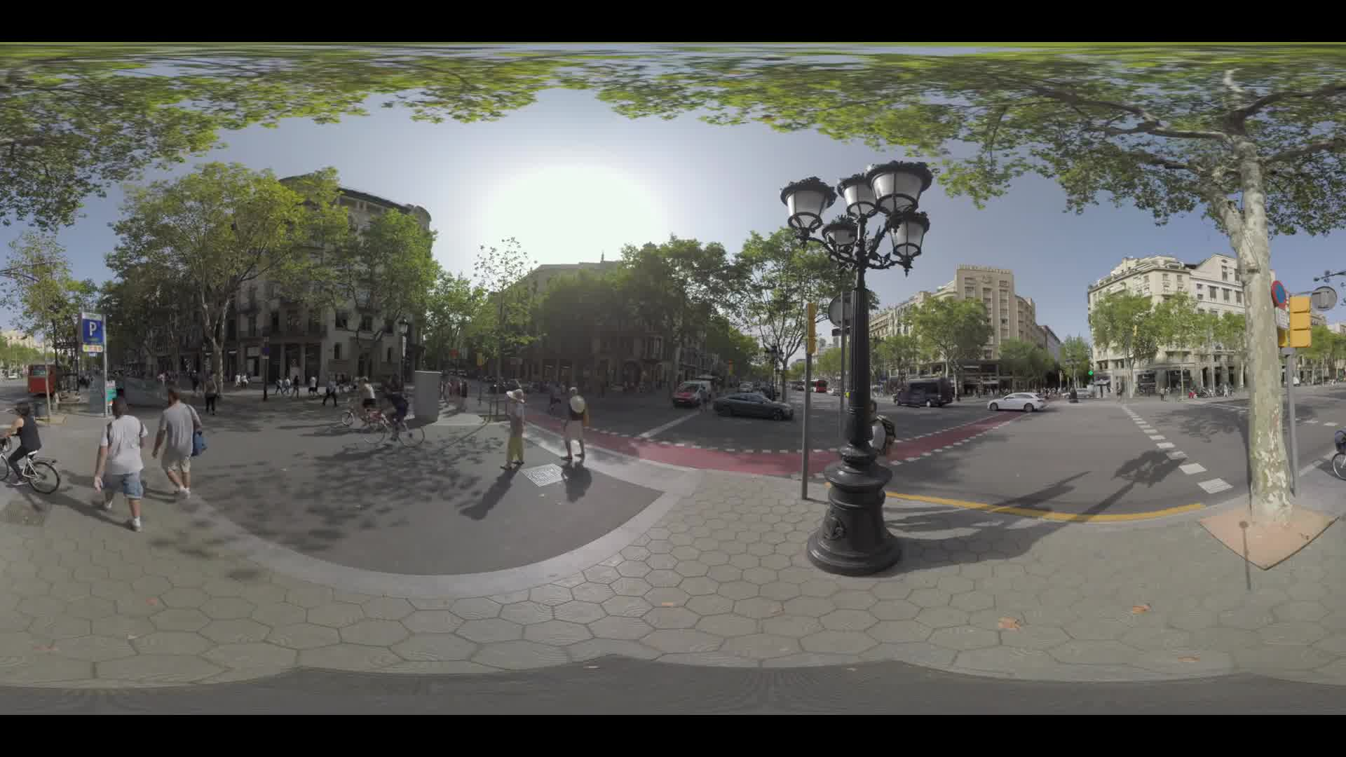 BARCELONA, SPAIN - JULY 29, 2016: 360 VR video. Transport traffic on busy junction in the city. People walking on sidewalks and crossing the roads. Cyclists using bike lanes