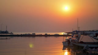 Cinemagraph - Sunset waterscape with harbour and tied up boats. Golden sunlight reflecting in water. Quiet marine scene