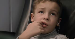 Close-up shot of a boy in earphones and finger in the mouth watching cartoons in the train