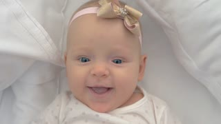 Close-up shot of six months old baby girl with a bow. Portrait of happy blue-eyed child lying on bed