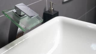 Closeup shot of modern sink tap, undefined person is washing hands with liquid soap under it.
