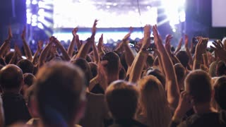 Crowd of anonymous people holding hands up and having fun during amazing musical show