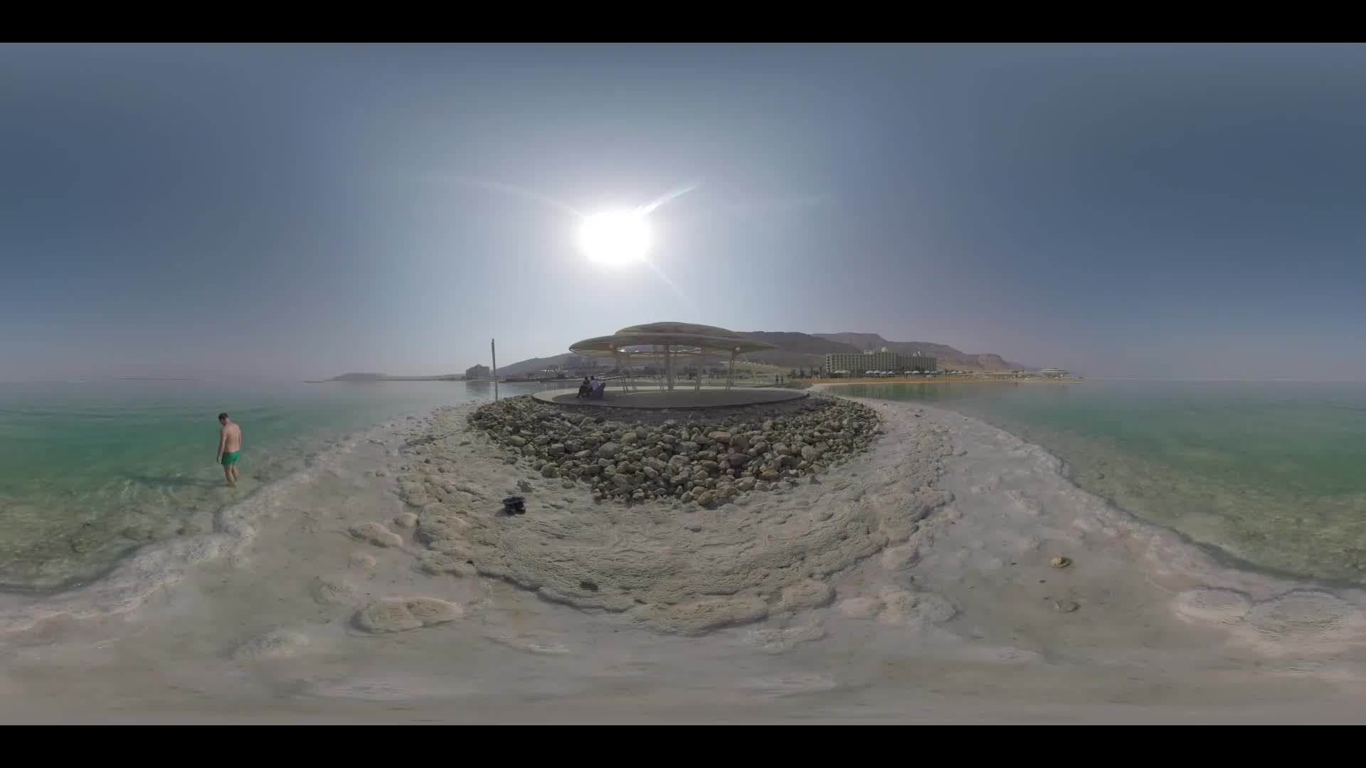 DEAD SEA, ISRAEL - MARCH 11, 2017: 360 VR video. Resort on the shore of Dead Sea. Man (with model release) bathing in pure salt water and some vacationers relaxing on the shaded deck nearby