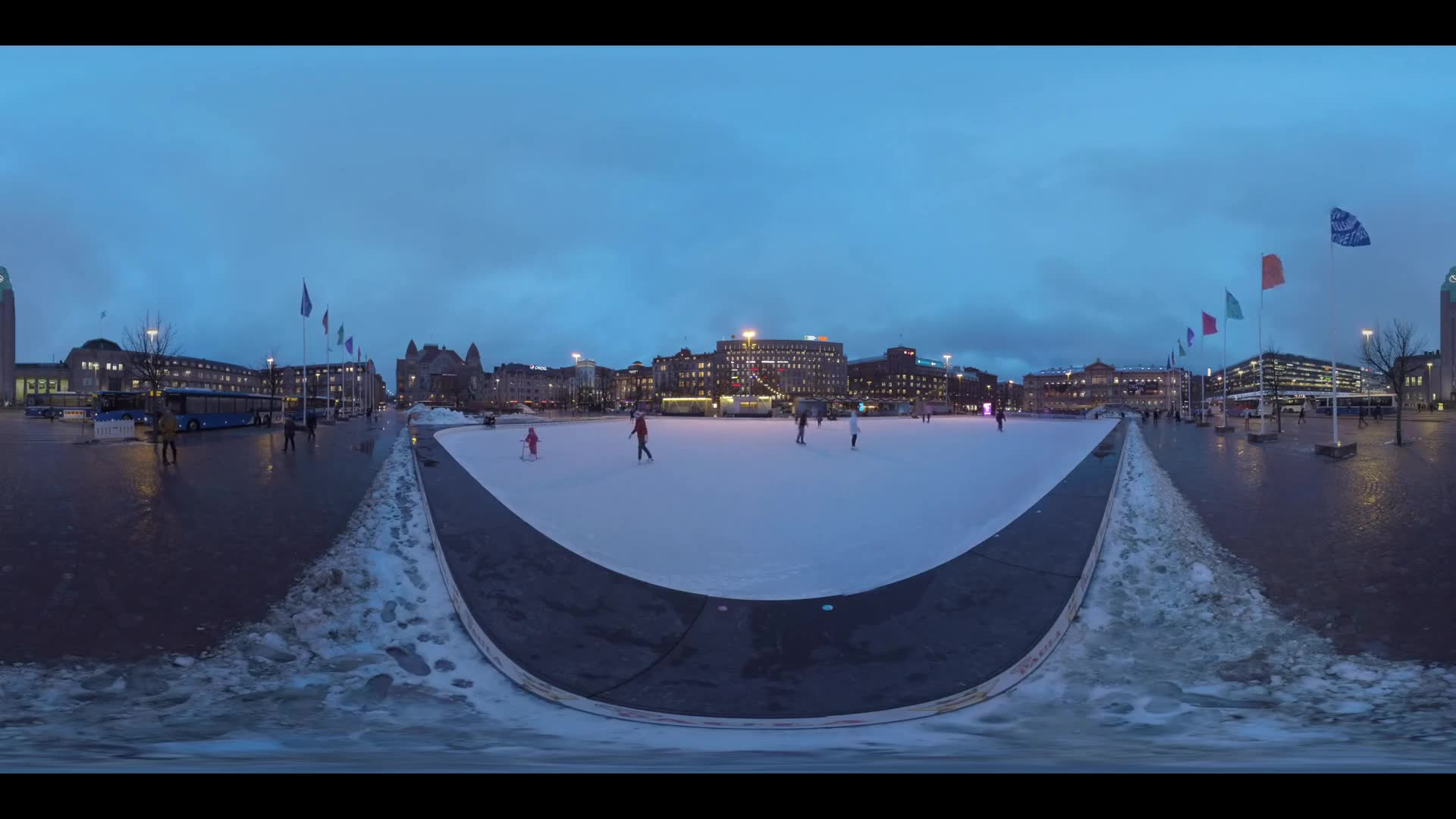 HELSINKI, FINLAND- JANUARY 05, 2016: 360 VR video. Evening cityscape with Railway Central Station. Adults and children skating on the ice rink at Railway Square that hosts also a bus station