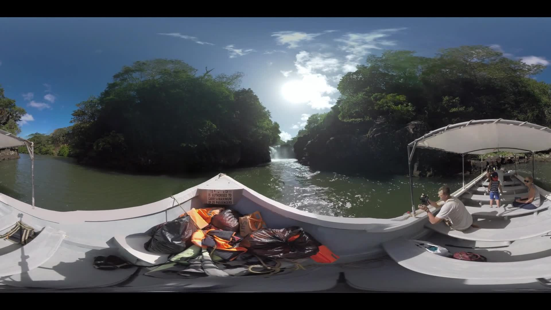 MAURITIUS ISLAND - JUNE 08, 2016: 360 VR video. Mom, dad and son (with model release) sailing by boat to see the waterfall. Woman and man tourists taking pictures with camera and cellphone