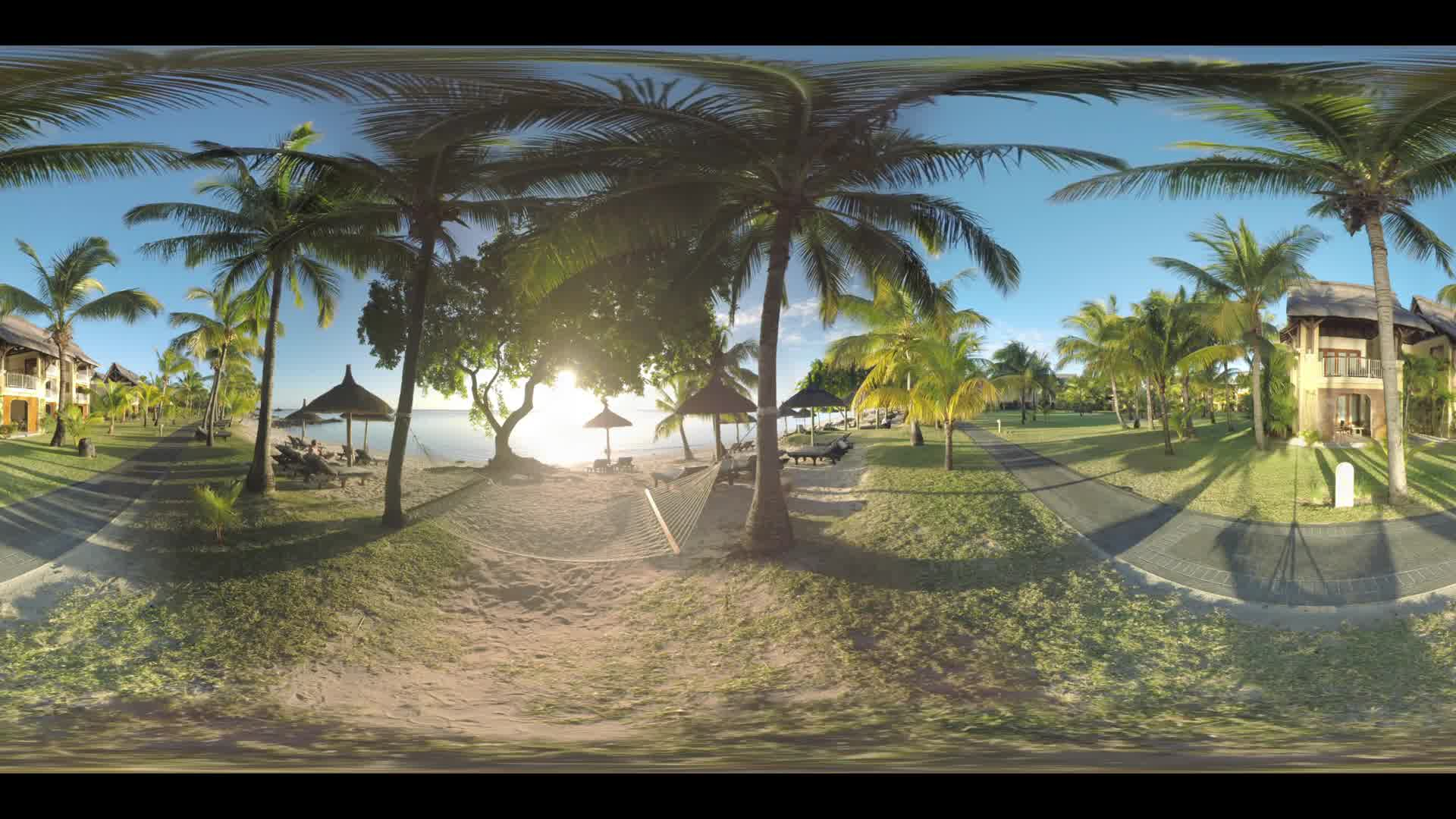 MAURITIUS ISLAND - JUNE 08, 2016: 360 VR video. Ocean beach with hammock, chaise-longues and straw umbrellas at sunset. Tropical resort with hotels and palms everywhere. People walking along the path and cart driving there