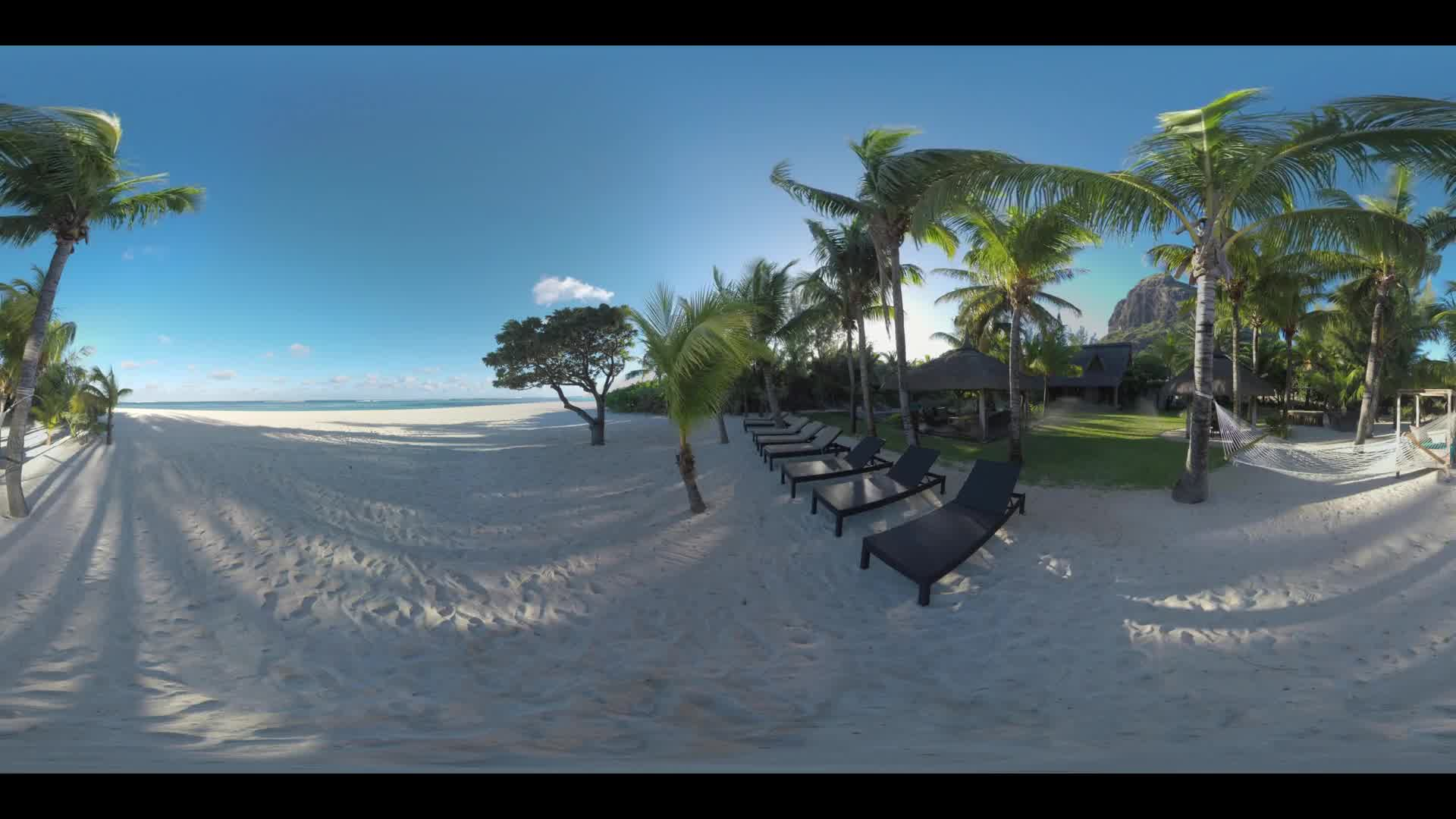 MAURITIUS ISLAND - JUNE 08, 2016: 360 VR video. Ocean skyline and beach with hammock, chaise-longues on tropical resort of Le Morne Brabant, Mauritius. Couple with dog walking along the coast