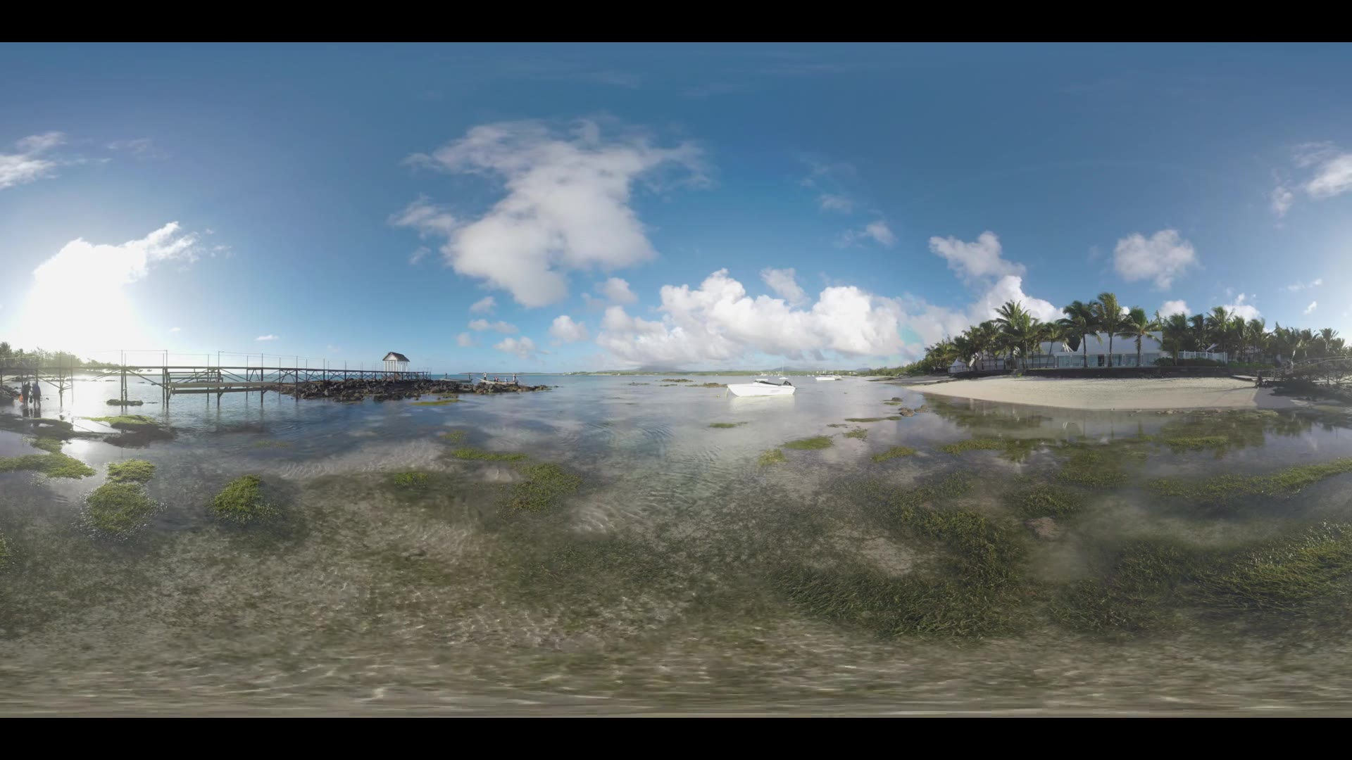 MAURITIUS ISLAND - JUNE 08, 2016: 360 VR video. View of beach line with palms, shallow water with boats and wooden pier in Mauritius on bright sunny day. People walking on the pier and in water