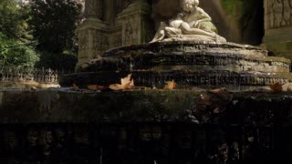 Medici Fountain with sculpture of Acis and Galatea and autumn leaves in water. Visiting Luxembourg Gardens in Paris, France
