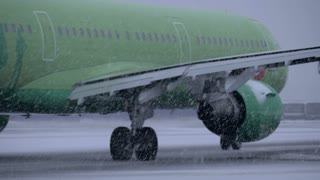 MOSCOW, RUSSIA - DECEMBER 18, 2017: Plane of S7 Airlines driving from runway in blizzard at Domodedovo Airport. S7 operates flights to 87 destinations all over Europe, the Middle East, Russia, and