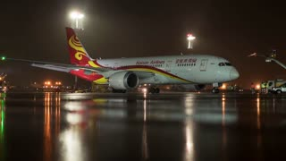 MOSCOW, RUSSIA - OCTOBER 31, 2017: Timelapse shot of servicing and deicing the airplane of Hainan Airlines before departure in Sheremetyevo Airport at night. The fourth-largest airline in Asia in