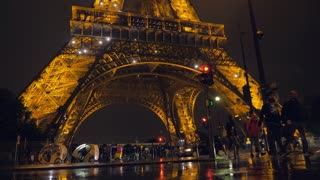 PARIS, FRANCE - SEPTEMBER 29, 2017: French capital at rainy night. Street view with driving cars and crosswalk near illuminated Eiffel Tower