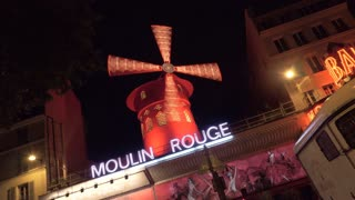 PARIS, FRANCE - SEPTEMBER 29, 2017: Night illuminated Moulin Rouge with zooming in spinning red mill. Filmed with a ghost effect. Cabaret offering world famous dance entertainment