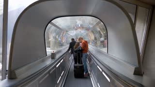 PARIS, FRANCE - SEPTEMBER 29, 2017: People with luggage moving on travelator through the glassy tunnel at Charles de Gaulle Airport, the largest international airport in France