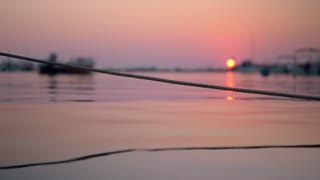 Rope in water tied up to the boat in harbour. Marine scene at sunset