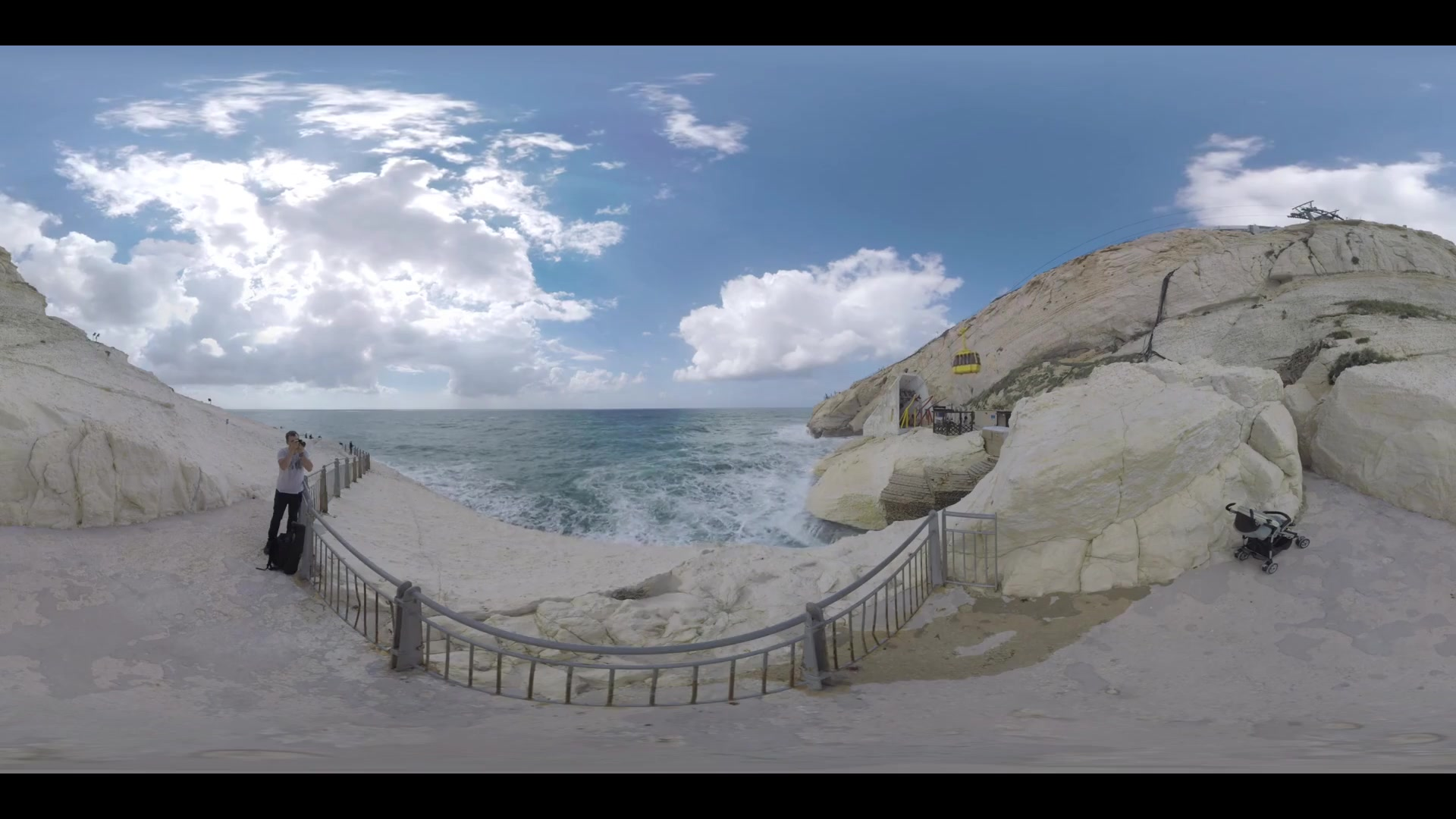 ROSH HANIKRA, ISRAEL - MARCH 12, 2017: 360 VR video. White chalk cliff meeting sea. Rosh HaNikra landscape with the steepest in the world cable car. Man tourist (with model release) taking shots of nature scene