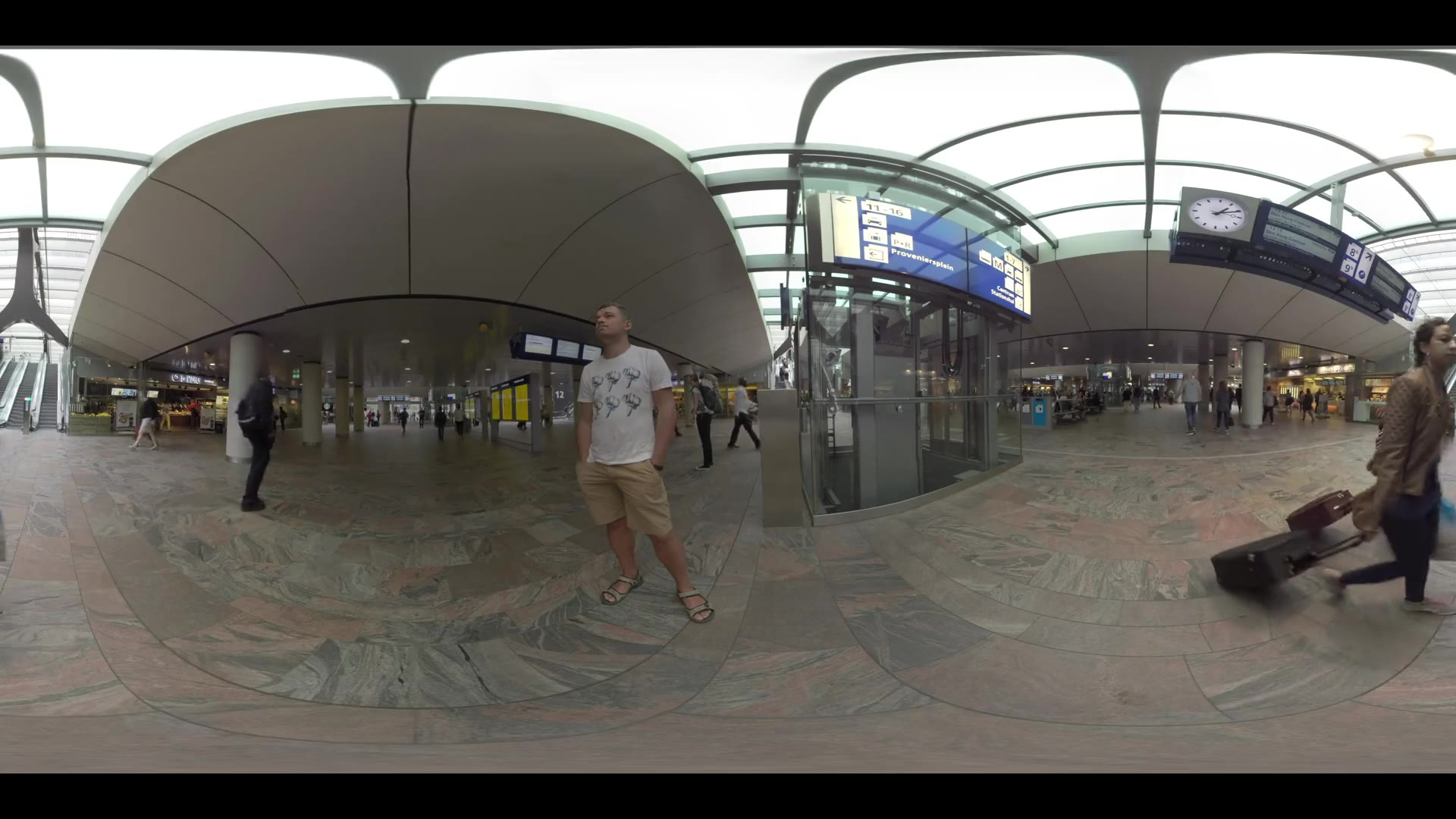 ROTTERDAM, NETHERLANDS - AUGUST 07, 2016: 360 VR video. Rotterdam Centraal station with walking people. Inside view with information screens overhead, entry and exit escalators