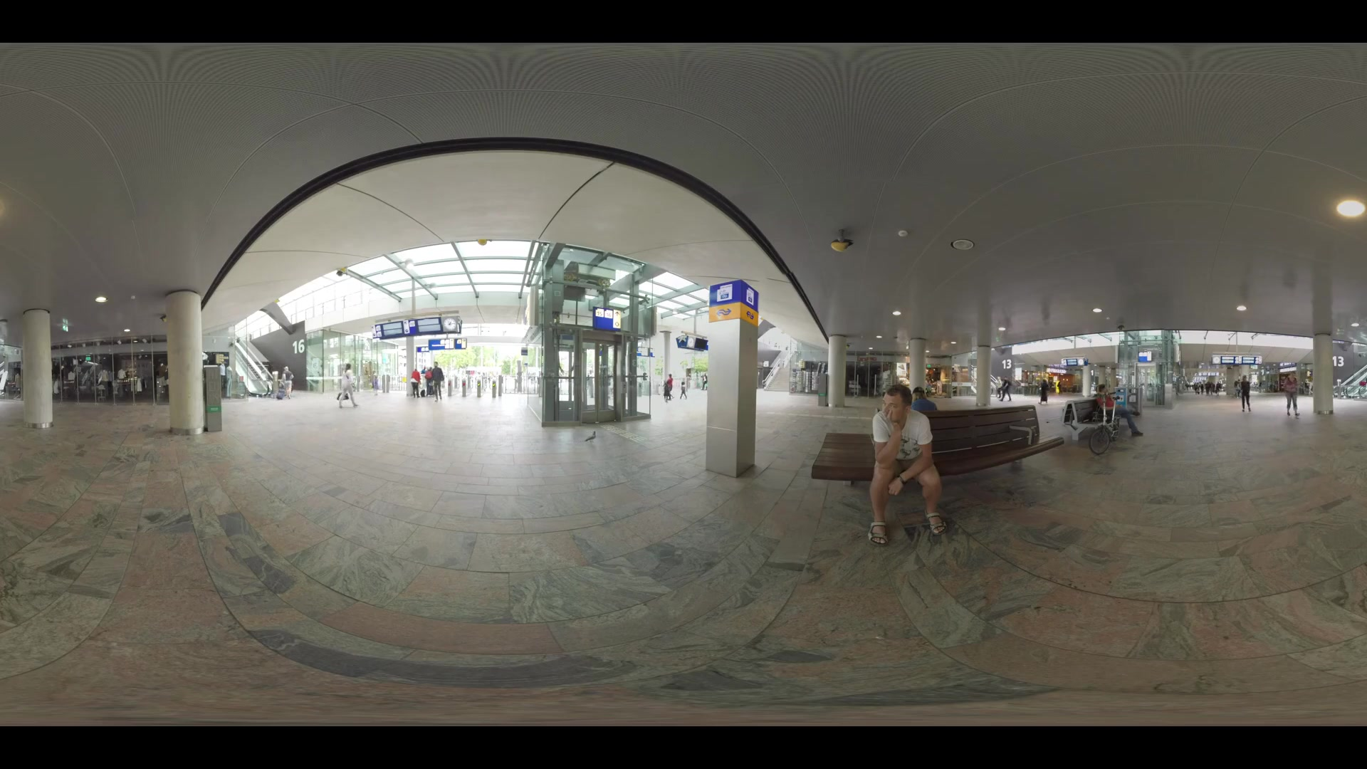ROTTERDAM, NETHERLANDS - AUGUST 07, 2016: 360 VR video. View inside Rotterdam Centraal station. Hall with elevators, several escalators and people walking to the exit