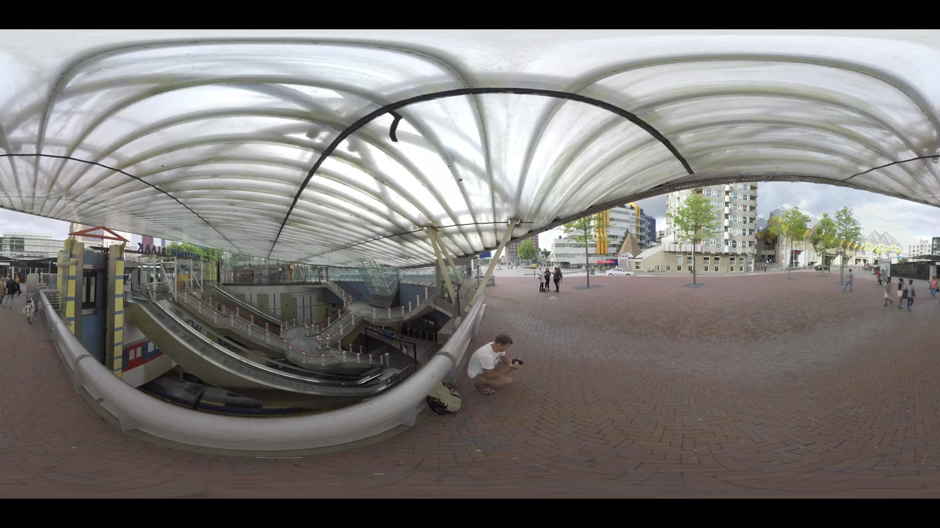 ROTTERDAM, NETHERLANDS - AUGUST 07, 2016: 360 VR video. View to the entrance of Blaak metro and railway station with escalators going up and down. Street with Central Library, Cube Houses and people walking by