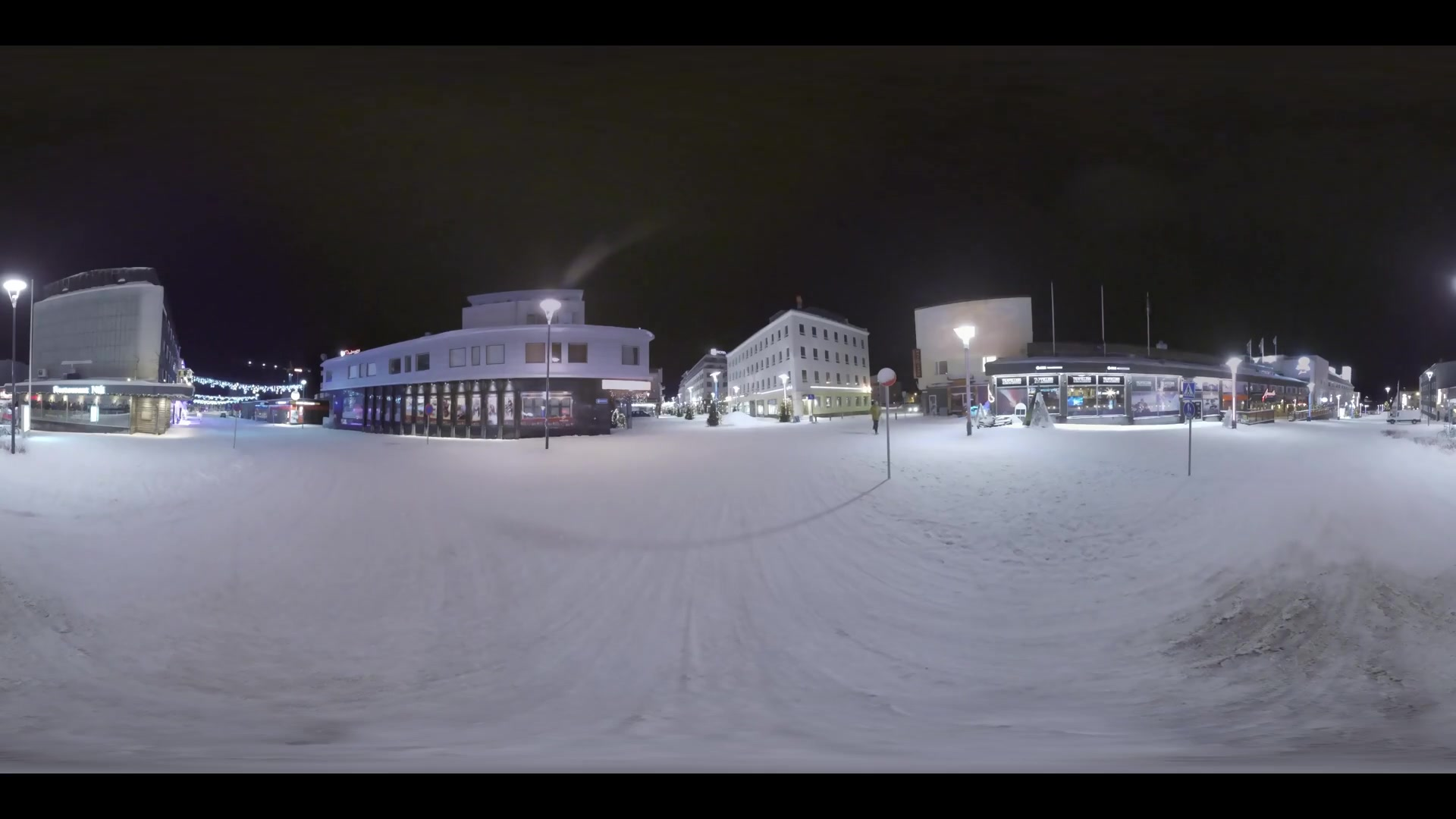 ROVANIEMI, FINLAND- JANUARY 01, 2017: 360 VR Video. Cityscape of night city in winter. Man (with model release) having a walk in snowy street illuminated with lanterns and Christmas decorations