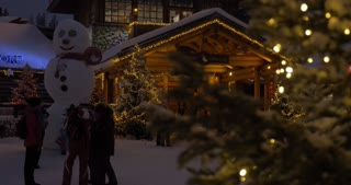 ROVANIEMI, FINLAND - JANUARY 06, 2017: Tilt shot of Santa Claus Office at Arctic Circle in Lapland. People and Christmas trees at the entrance, night shot