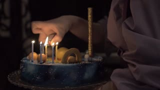 Slow motion shot of a mother lighting the candles on birthday cake in the darkness. Making a wish on special day