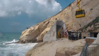 Slow motion shot of sea waves crushing white chalk cliffs, moving funicular and tourists enjoying landscape at Rosh Hanikra