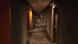 Speed-up video of walking through the empty hotel hallway to the room. Grey and orange interior design