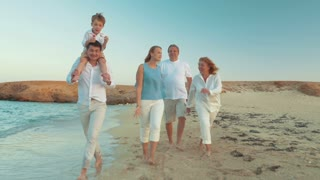 Steadicam shot of happy barefoot family walking along the coast. Child sitting on fathers neck and blowing soap bubbles. Carefree time on vacation