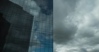 Timelapse shot of clouds sailing in the sky and reflecting in modern glassy business centre
