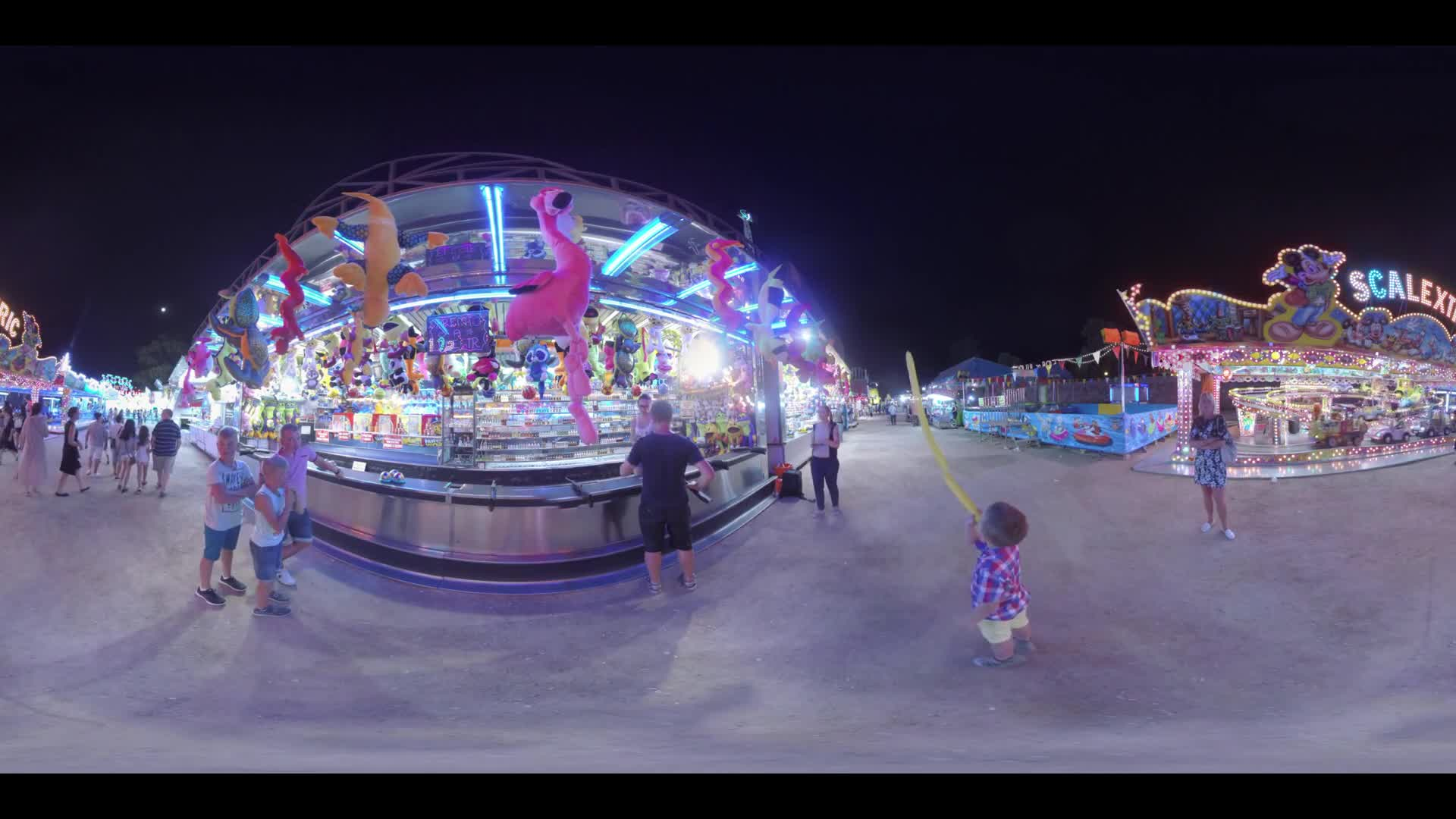 VALENCIA, SPAIN - JULY 15 2016: 360 VR video. People entertaining in amusement park at night. There are many illuminated fairground attractions. Man and his family (with model release) trying to win prize in shooting gallery