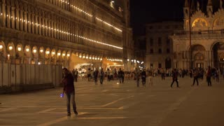 VENICE, ITALY - APRIL 23, 2018: San Marco Square. Night view with illuminated ancient building, walking people and vendors flying luminous toys