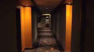 Walking through the empty hallway in the hotel. Interior design in dark grey and orange colors