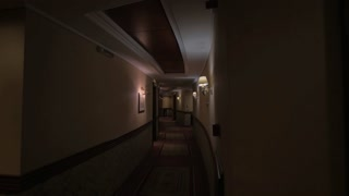 View of round hotel corridor with lighted lamps. View of two walls and room doors in the hall. Greece
