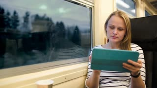 Woman sitting by the window in the train in the evening. She using tablet PC and drinking tea, sometimes looking out the window