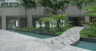 Woman with tablet PC walking across the garden with decorative waterfalls near the house or hotel in Kuala Lumpur, Malaysia
