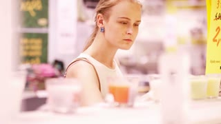 Young blond woman smelling scented candles in the store