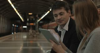 Young couple is waiting for the train in the metro station. They are watching something in tablet PC and discussing it emotionally.