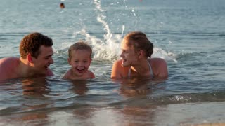 Young family splashing in the sea with attractive parents flanking their small son lying in the shallow surf in the summer sun