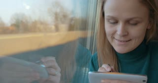 Young female passenger in the train typing sms on smart phone with a pen.  After taking it away she enjoying view from the window