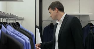 Young man in suit is looking price labels in menswear store.