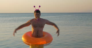 Young man with funny ears and rubber ring making a humorous show with dancing on the beach
