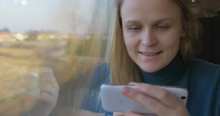 Young smiling woman traveling by train. She using smart phone with a pen and then enjoying the scene from the window