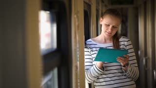 Young smiling woman using tablet PC standing near the window in train hallway