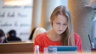 Young woman in cafe using her touchpad, defocused people in the background