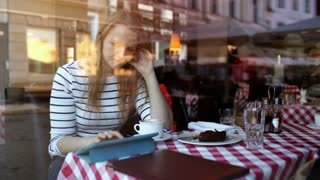 Young woman in cafe using touchpad and eating dessert. View through the glass with reflection of city and people