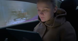 Young woman using tablet computer while traveling by car on dull day