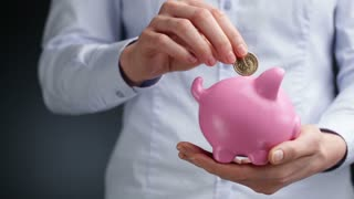 A young businesswoman holds a pink piggy bank and puts a 1 US dollar coin in it.